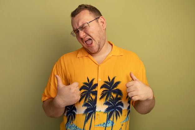 Zadowolony mężczyzna w okularach w pomarańczowej koszuli, wskazujący na siebie uśmiechnięty i mrugający, stojący nad zieloną ścianą