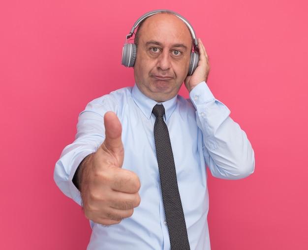 Zadowolony mężczyzna w średnim wieku ubrany w białą koszulkę z krawatem i słuchawkami pokazujący kciuk w górę na różowej ścianie