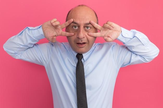 Zadowolony mężczyzna w średnim wieku ubrany w białą koszulkę z krawatem przedstawiający gest pokoju na różowej ścianie