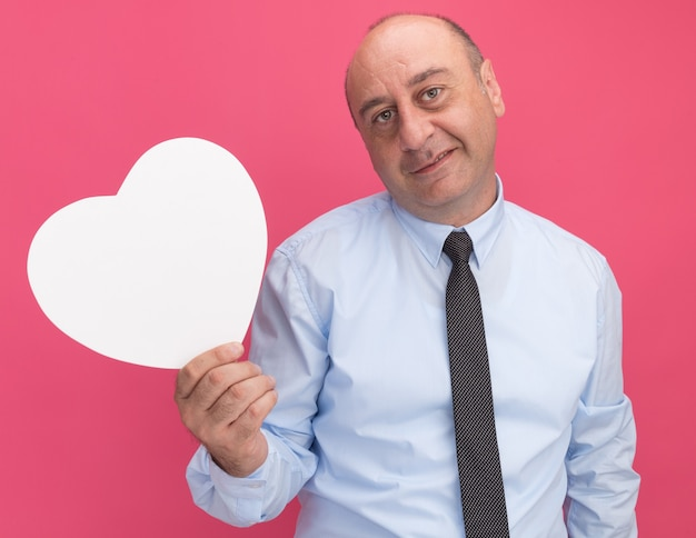 Zadowolony mężczyzna w średnim wieku, ubrany w białą koszulkę z krawatem, trzymający pudełko w kształcie serca na różowej ścianie