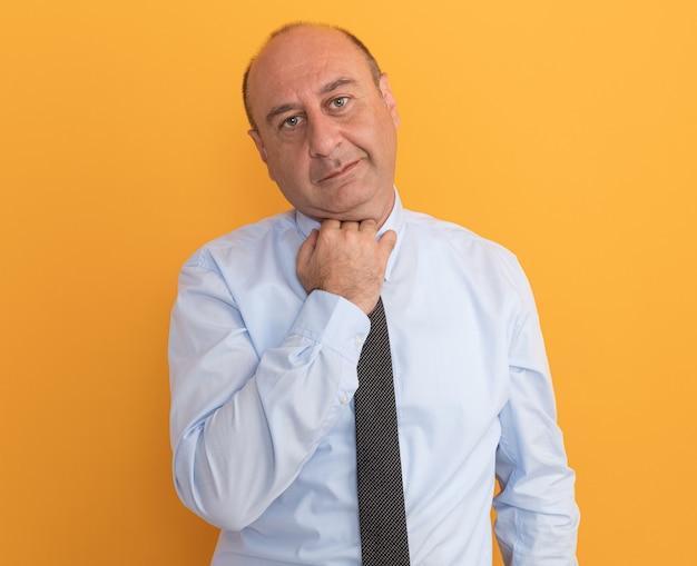Zadowolony mężczyzna w średnim wieku ubrany w białą koszulkę z krawatem z kołnierzykiem na białym tle na pomarańczowej ścianie