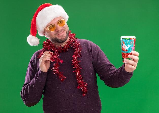Zadowolony mężczyzna w średnim wieku w czapce świętego mikołaja i świecącej girlandzie na szyi z okularami wyciągającymi plastikowy świąteczny kubek patrząc na niego dotykając świecącej girlandy na zielonej ścianie