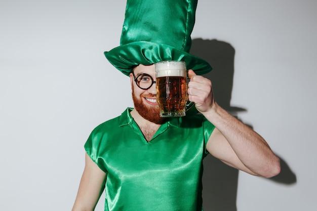 Zadowolony mężczyzna w st. kostiumach patrickich trzyma piwo