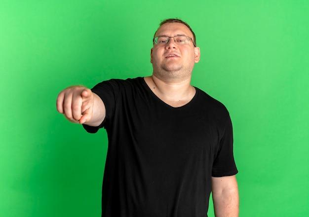 Zadowolony mężczyzna z nadwagą w okularach na sobie czarną koszulkę, wskazując palcem uśmiechnięty stojący nad zieloną ścianą
