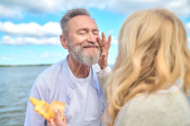 Zadowolony mężczyzna z zamkniętymi oczami i kobieta dotykająca dłoni