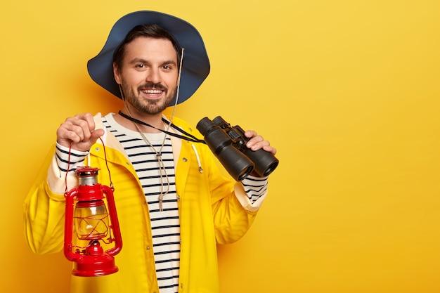 Zadowolony mężczyzna z zarostem, nosi nakrycie głowy i żółty płaszcz przeciwdeszczowy, nosi lampę naftową i lornetkę, z radością patrzy na aparat, stoi w pomieszczeniu