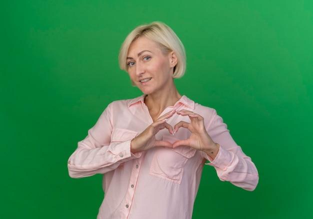 Zadowolony młoda blond słowiańska kobieta robi znak serca w aparacie na białym tle na zielonym tle