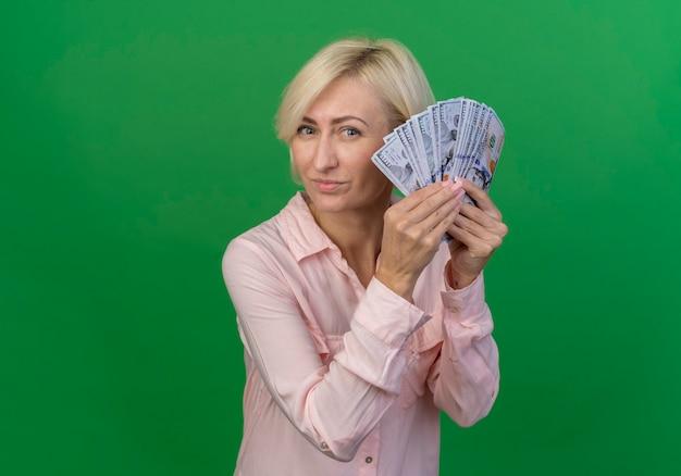 Zadowolony młoda blond słowiańska kobieta trzyma pieniądze patrząc na kamery na białym tle na zielonym tle z miejsca na kopię