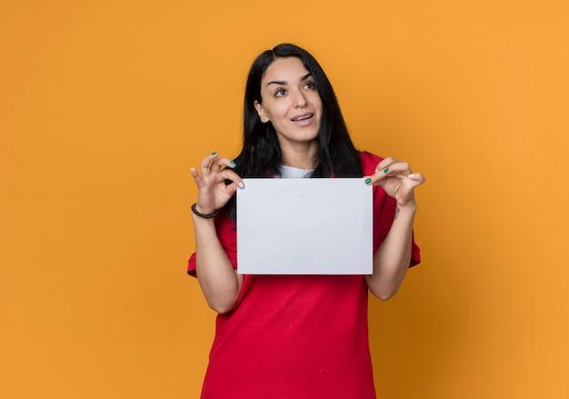 Zadowolony młoda brunetka kaukaski dziewczyna ubrana w czerwoną koszulę trzyma pusty arkusz papieru, patrząc z boku na białym tle na pomarańczowej ścianie