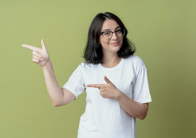Zadowolony młoda dziewczyna całkiem kaukaski w okularach, wskazując na bok na białym tle na oliwkowym tle z miejsca kopiowania