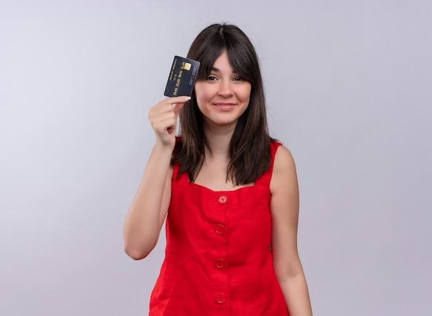 Zadowolony młoda dziewczyna kaukaski trzymając kartę kredytową i patrząc na kamery na na białym tle