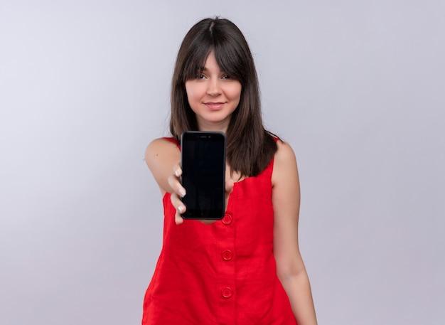 Zadowolony młoda dziewczyna kaukaski trzymając telefon prosto i patrząc na kamery na na białym tle