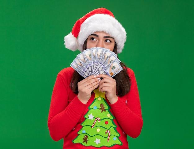 Zadowolony młoda dziewczyna kaukaski z santa hat trzyma pieniądze patrząc na bok na białym tle na zielonym tle z miejsca na kopię