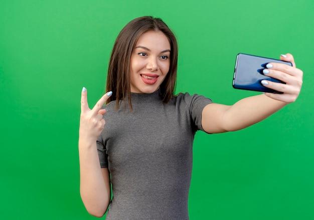 Zadowolony młoda ładna kobieta robi znak pokoju i biorąc selfie na zielono