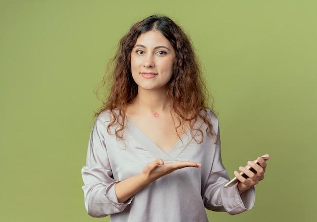 Zadowolony, młoda ładna pracownica biurowa trzyma i wskazuje ręką na telefon na białym tle na oliwkowej ścianie
