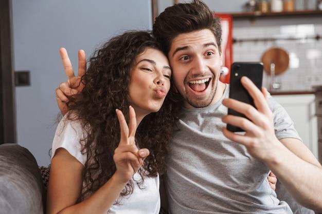Zadowolony młoda para mężczyzna i kobieta siedzą na kanapie w domu i robią razem zdjęcie selfie na smartfonie