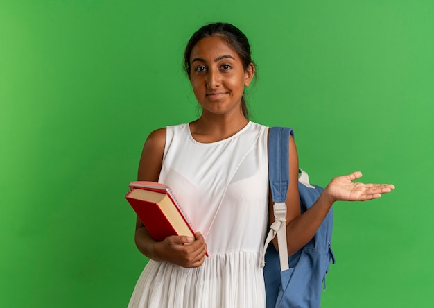 Zadowolony młoda uczennica ubrana w plecak trzymając książkę z notatnikiem i rozłożoną ręką na białym tle na zielono
