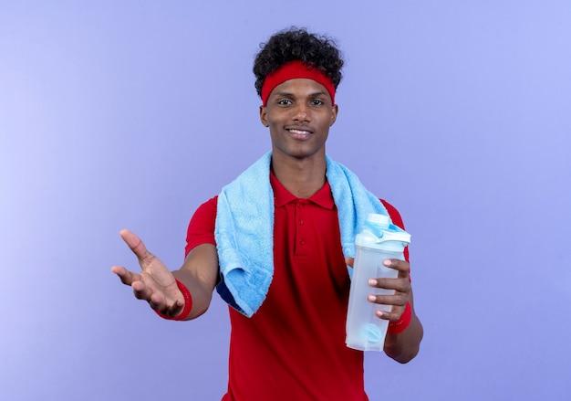 Zadowolony młody afro-amerykanin wysportowany mężczyzna noszący opaskę na głowę i nadgarstek trzymający butelkę z wodą wyciągniętą ręką do aparatu z ręcznikiem na ramieniu
