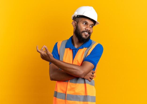 Zadowolony młody afro-amerykański budowniczy mężczyzna w mundurze z hełmem ochronnym, patrząc na bok na białym tle na pomarańczowym tle z kopią przestrzeni