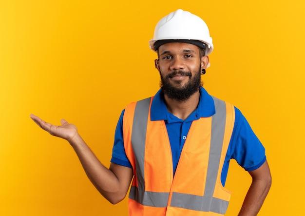 Zadowolony młody afro-amerykański budowniczy mężczyzna w mundurze z hełmem ochronnym, udając, że trzyma coś na białym tle na pomarańczowym tle z kopią przestrzeni