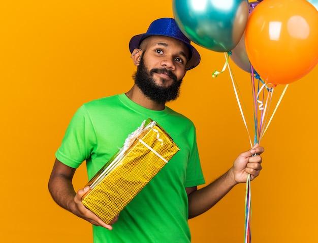 Zadowolony młody afro-amerykański facet w kapeluszu imprezowym, trzymający balony z pudełkiem prezentowym odizolowanym na pomarańczowej ścianie