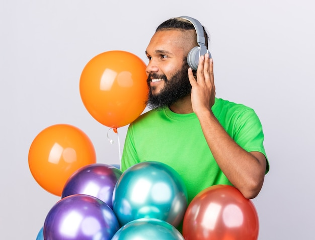 Zadowolony młody afro-amerykański facet w słuchawkach odizolowanych na białej ścianie