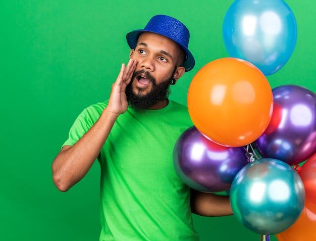 Zadowolony młody afroamerykanin w kapeluszu imprezowym trzymający balony wołający kogoś