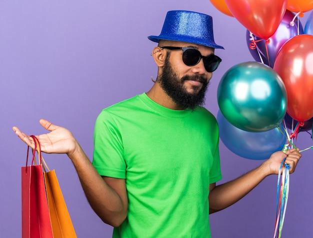 Zadowolony młody afroamerykanin w kapeluszu imprezowym w okularach, trzymający balony z torbą na prezenty