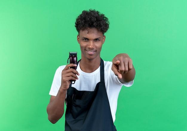 Zadowolony młody afroamerykański fryzjer męski ubrany w mundur trzymający maszynkę do strzyżenia włosów i pokazujący gest