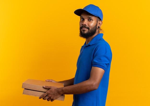 Zadowolony młody afroamerykański mężczyzna dostawy stojący bokiem, trzymający pudełka po pizzy na białym tle na pomarańczowym tle z miejscem na kopię copy