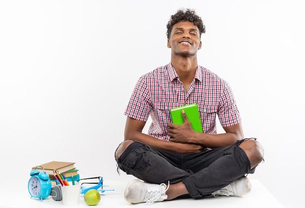 Zadowolony młody afroamerykański uczeń siedzący na biurku z szkolnymi narzędziami trzymającymi książkę