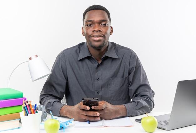 Zadowolony młody afroamerykański uczeń siedzący przy biurku z szkolnymi narzędziami trzymającymi telefon
