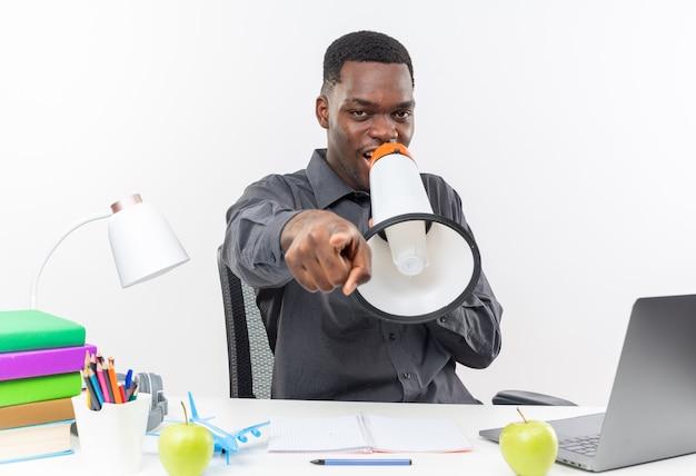 Zadowolony młody afroamerykański uczeń siedzący przy biurku ze szkolnymi narzędziami mówiący do głośnika i wskazujący na przód