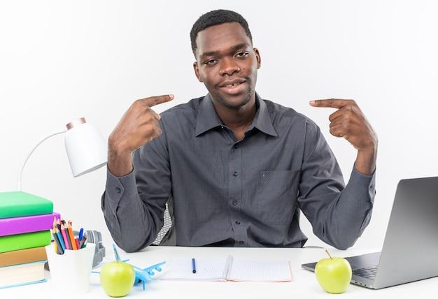 Zadowolony młody afroamerykański uczeń siedzący przy biurku ze szkolnymi narzędziami wskazującymi na siebie