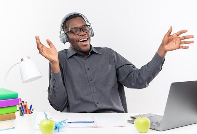 Zadowolony młody afroamerykański uczeń w okularach optycznych i na słuchawkach, siedząc przy biurku z narzędziami szkolnymi, trzymając ręce otwarte na białym tle na białej ścianie