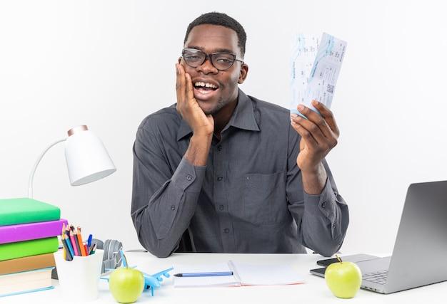 Zadowolony młody afroamerykański uczeń w okularach optycznych siedzący przy biurku z szkolnymi narzędziami kładący rękę na twarzy i trzymający bilety lotnicze izolowane na białej ścianie