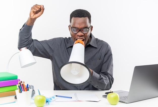 Zadowolony młody afroamerykański uczeń w okularach optycznych siedzący przy biurku z szkolnymi narzędziami mówiącymi do głośnika i podnoszący pięść na białym tle na białej ścianie
