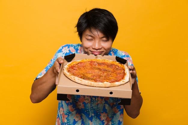 Zadowolony młody azjatycki mężczyzna stojący na białym tle nad żółtą przestrzenią, trzymając zapach pizzy.