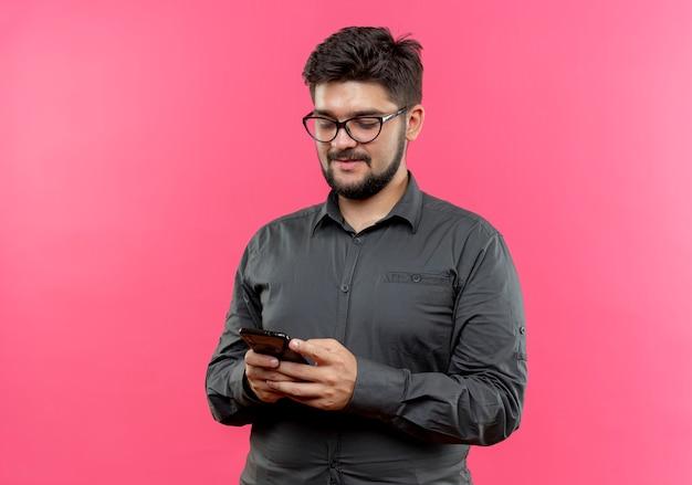 Zadowolony młody biznesmen w okularach, trzymając i patrząc na telefon na białym tle na różowej ścianie