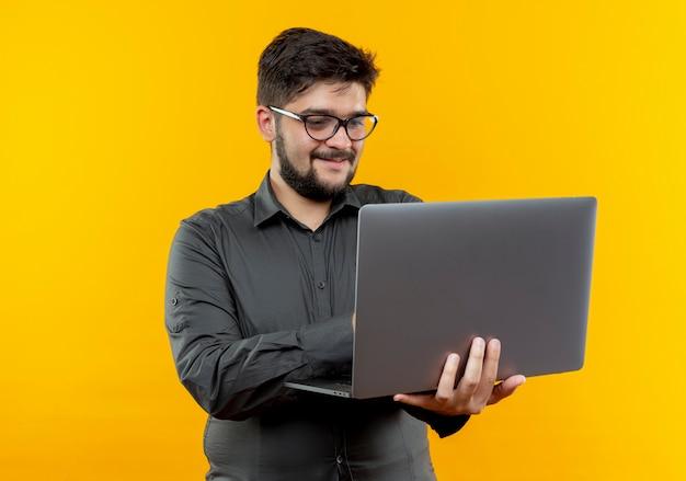 Zadowolony młody biznesmen w okularach, trzymając i używane laptop na białym tle na żółtym tle