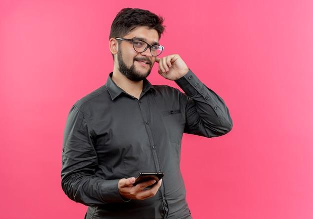 Zadowolony młody biznesmen w okularach trzymając telefon kładąc palec na uchu na białym tle na różowej ścianie
