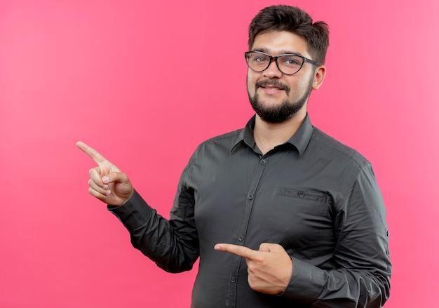 Zadowolony młody biznesmen w okularach wskazuje na bok na białym tle na różowej ścianie z miejsca na kopię