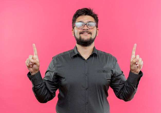 Zadowolony młody biznesmen w okularach wskazuje na górę odizolowane na różowo z miejsca na kopię