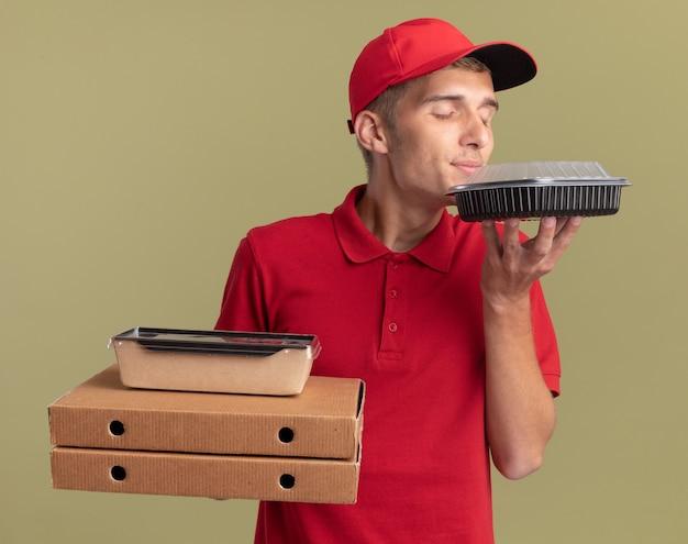 Zadowolony młody blond chłopiec dostarczający jedzenie trzyma opakowania żywności na pudełkach po pizzy i wącha pojemnik na jedzenie na białym tle na oliwkowozielonej ścianie z miejscem na kopię