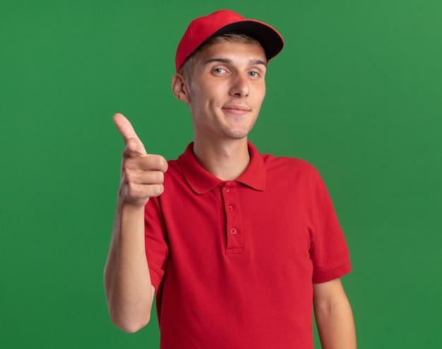 Zadowolony młody blond chłopiec-dostawca wskazuje w aparacie.