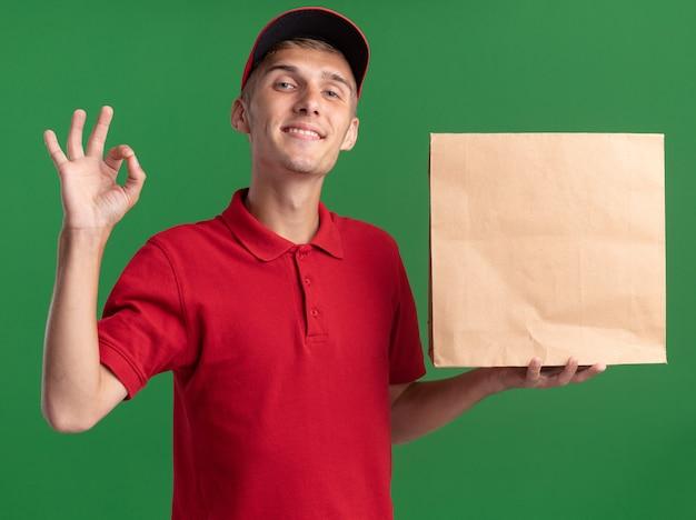 Zadowolony młody blond chłopiec dostawczy gestykuluje ok, znak ręką i trzyma papierowy pakiet