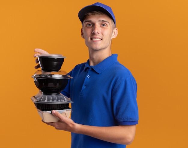 Zadowolony młody blond chłopiec z dostawą stoi bokiem, trzymając pojemniki na żywność