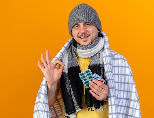 Zadowolony młody blond chory słowiański mężczyzna w czapce zimowej i gestach szalika w porządku znak ręką i trzyma paczkę tabletek medycznych zawiniętych w kratę na pomarańczowej ścianie z miejscem na kopię