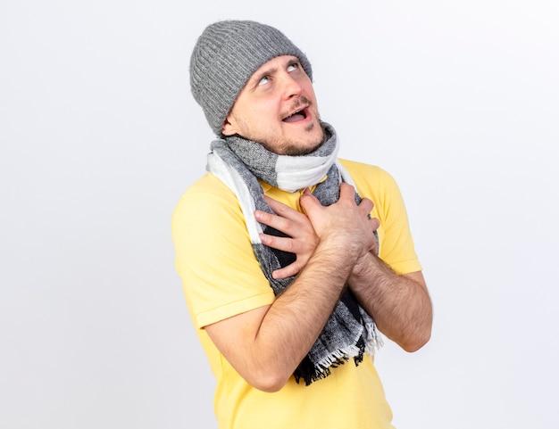 Zadowolony młody blond chory słowiański mężczyzna w czapce zimowej i szaliku kładzie ręce na klatce piersiowej, patrząc w górę na białej ścianie z miejscem na kopię