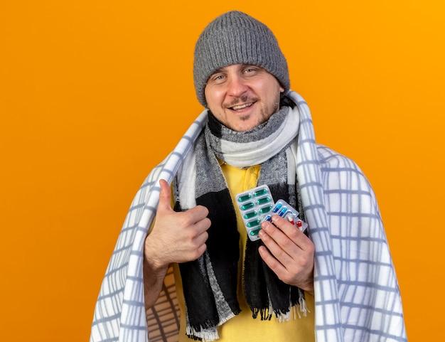 Zadowolony młody blond chory słowiański mężczyzna w czapce zimowej i szaliku owiniętym w kraciaste kciuki do góry i trzyma paczki pigułek medycznych odizolowane na pomarańczowej ścianie z miejscem na kopię